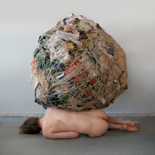 nude woman, prone, burdened by a sphere of garbage